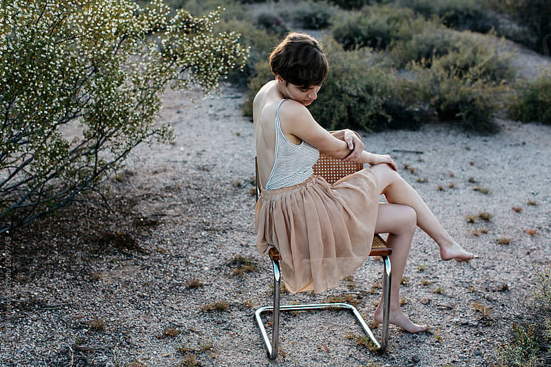 Girl sitting on a chair in the desert by Matt and Tish for Stocksy United