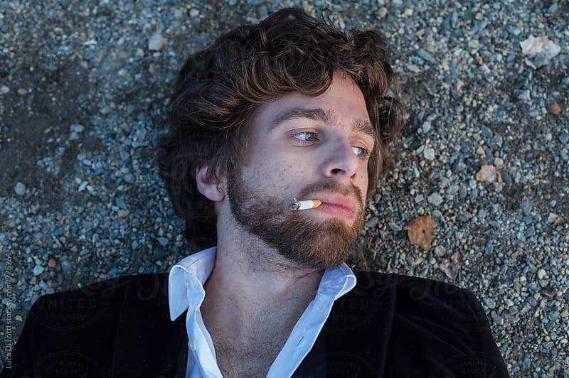 Young handsome man lying down on a pebbles beach smoking a cigarette, looking away. by Luca Di Lotti for Stocksy United