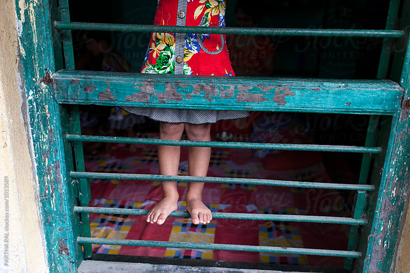 A little girl climbing in a rod of window by PARTHA PAL for Stocksy United