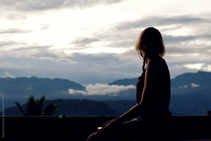 Woman staring over the rainforest during a cloudy sunset  by Denni Van Huis for Stocksy United
