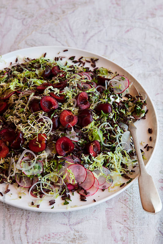 Plate of black rice salad with shaved brussel sprouts, cherries, red onion and radish by Nadine Greeff for Stocksy United