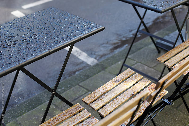 wet chairs and table in street by Rene de Haan for Stocksy United