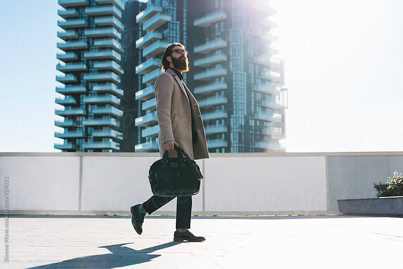 Businessman walking in the city by Simone Becchetti for Stocksy United