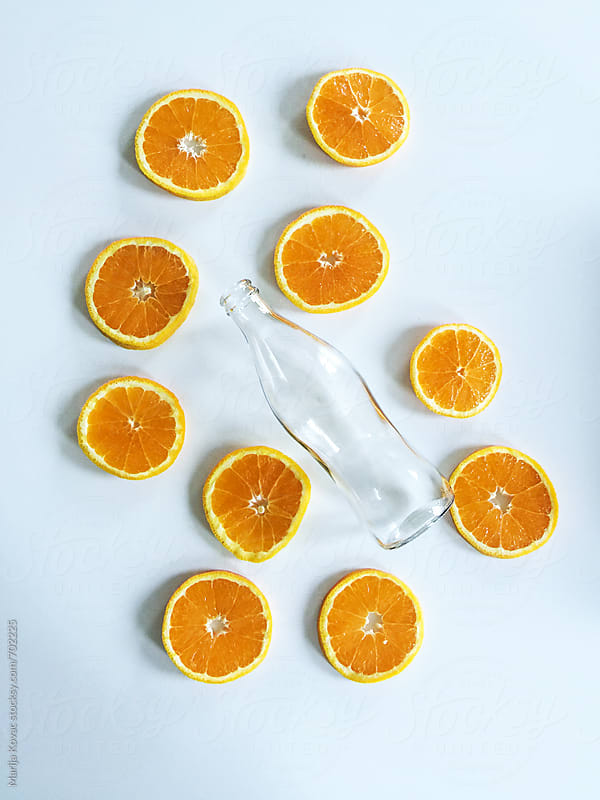 Empty bottle and slices of an orange on a white table by Marija Kovac for Stocksy United