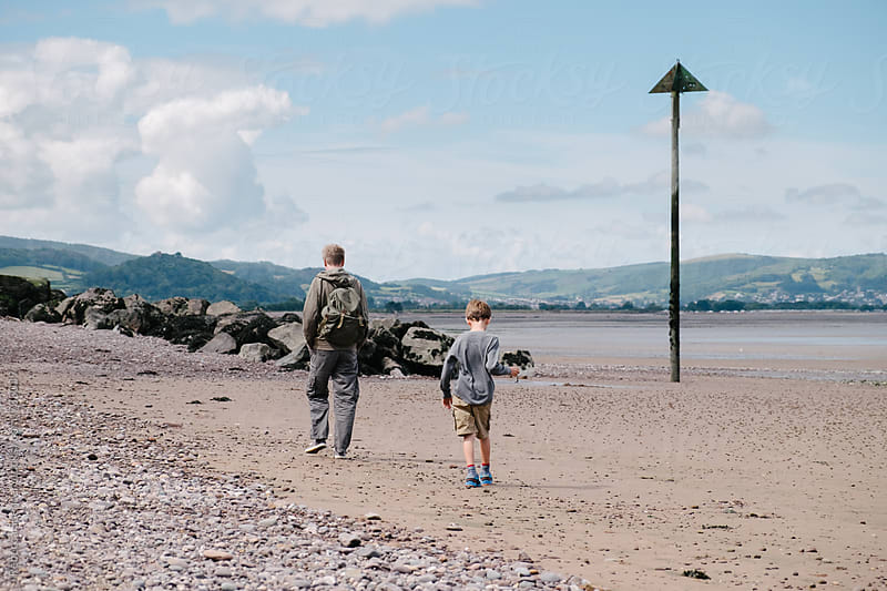 Father and son walking along the beach by Rebecca Spencer for Stocksy United