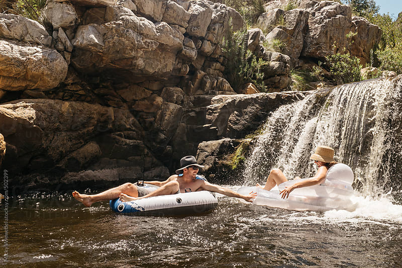 couple floating and playing on inflatable lilo's in a river by Micky Wiswedel for Stocksy United