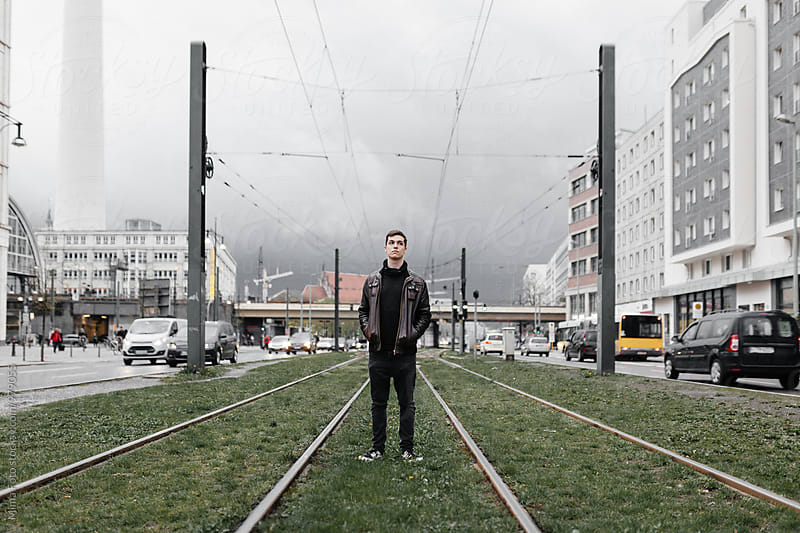 Teenager standing in urban traffic scene in Berlin, Germany by Mima Foto for Stocksy United