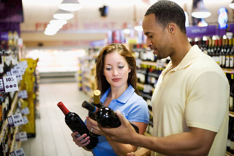 Supermarket: Couple Choosing Wine to Buy by Sean Locke for Stocksy United