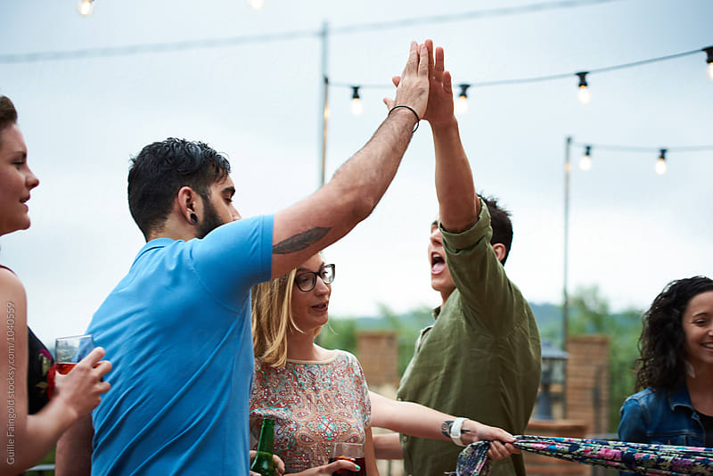 Men giving high five at party in garden by Guille Faingold for Stocksy United