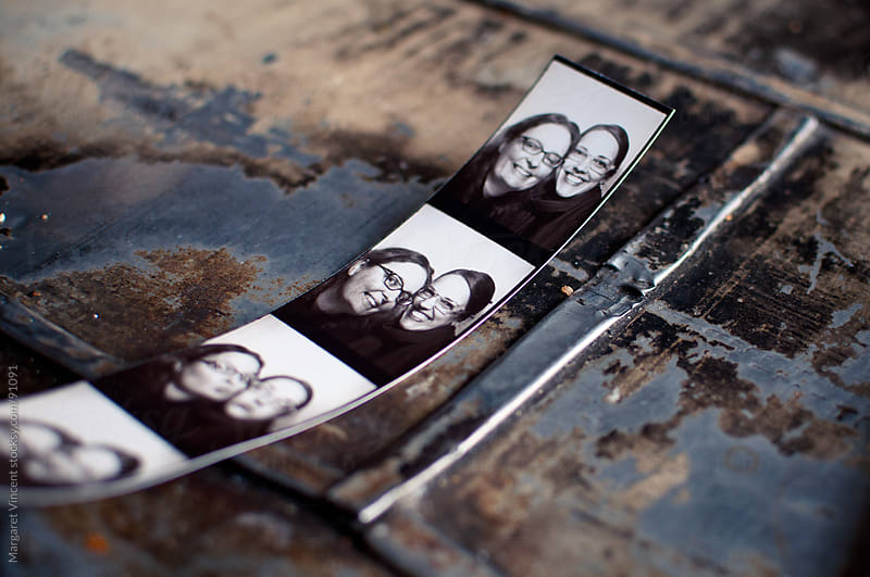 photos of two friends from a photo booth by Margaret Vincent for Stocksy United