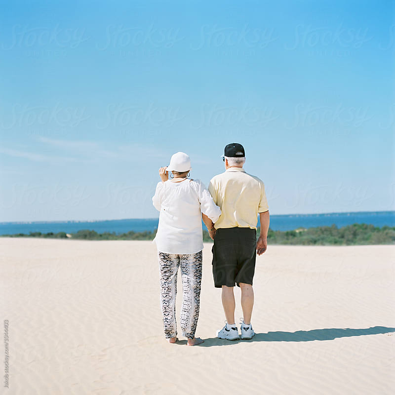 An older couple arm in arm on a sand dune looking towards an ocean by Jakob for Stocksy United