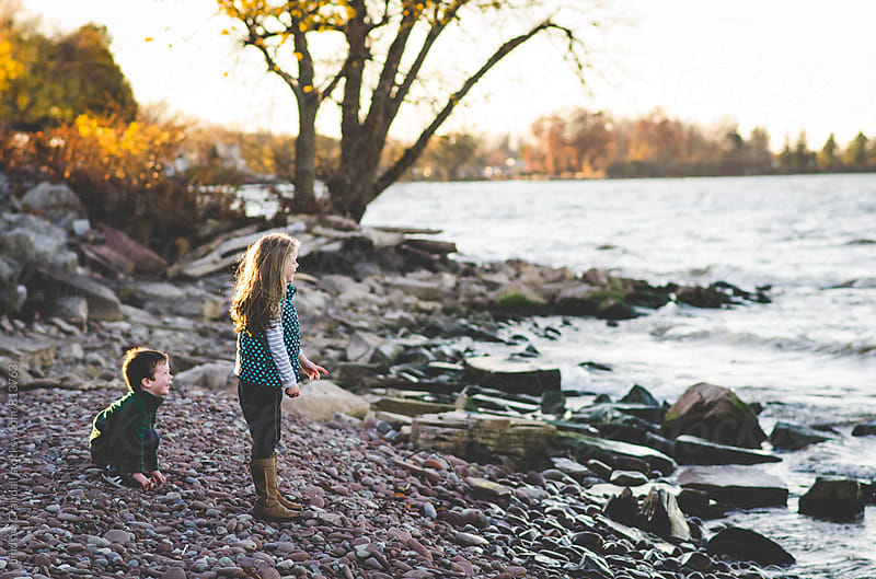 Boy and girl throwing rocks on the beach by Lindsay Crandall for Stocksy United