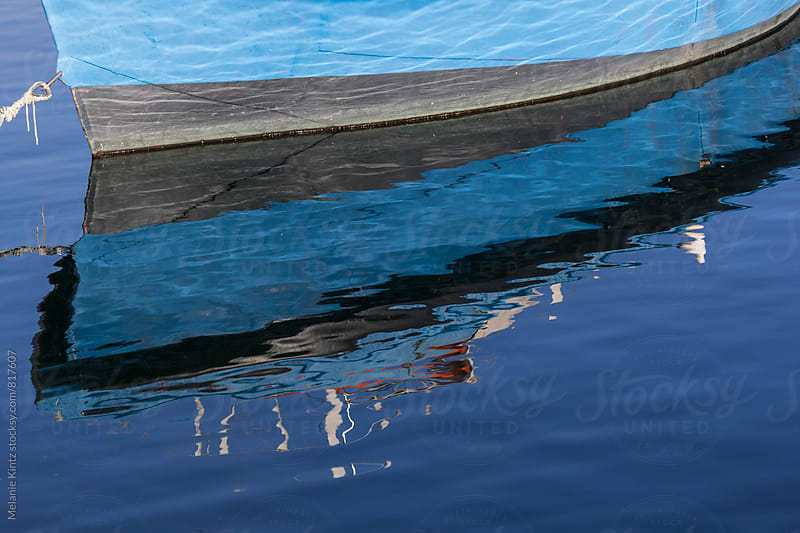 Blue boat reflecting in sea by Melanie Kintz for Stocksy United