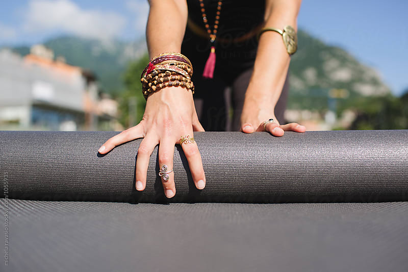 Woman rolls up the yoga mat by michela ravasio for Stocksy United