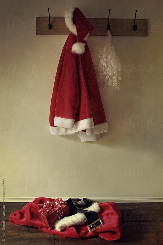 Santa costume hanging on coat rack  by Sandra Cunningham for Stocksy United