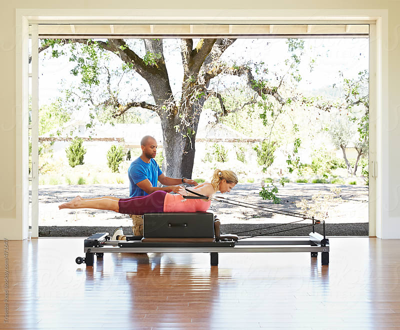 Woman doing pilates at luxury resort  by Trinette Reed for Stocksy United