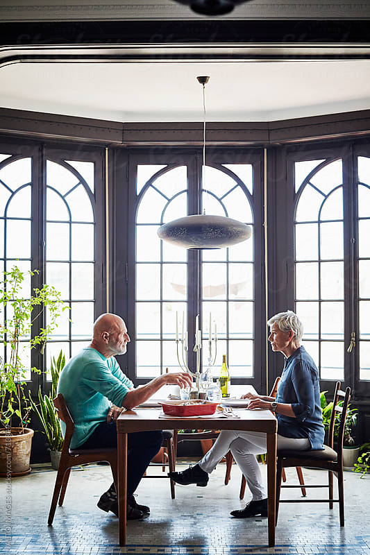 Senior Couple Having Lunch At Dining Table by ALTO IMAGES for Stocksy United