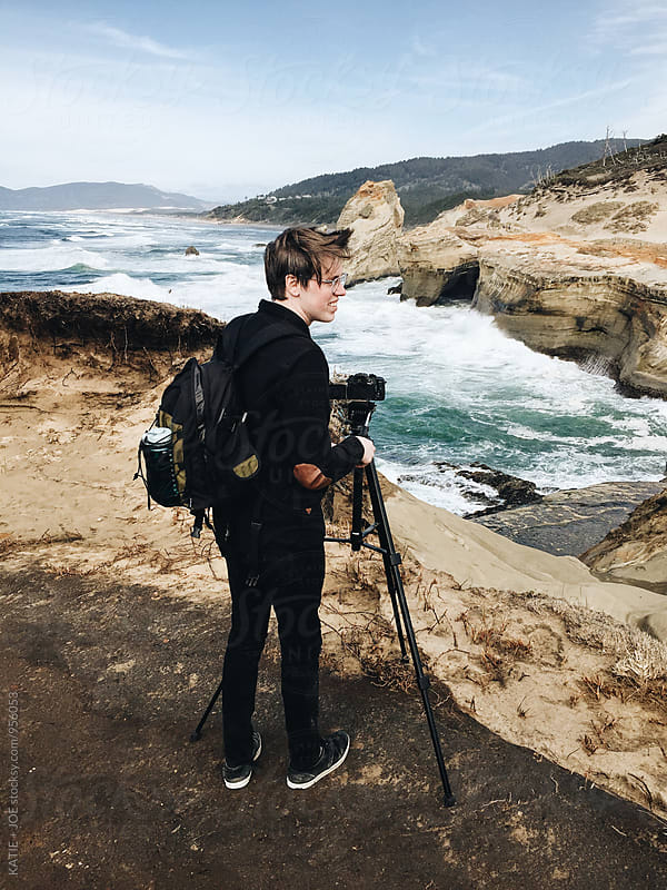 man standing on the edge of a cliff near the ocean with a tripod by KATIE + JOE for Stocksy United