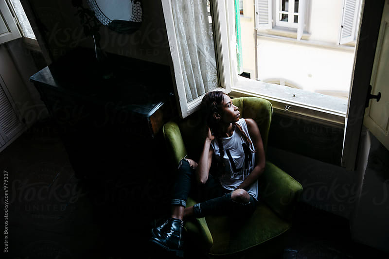 Young black woman with attitude sitting in an armchair by Beatrix Boros for Stocksy United
