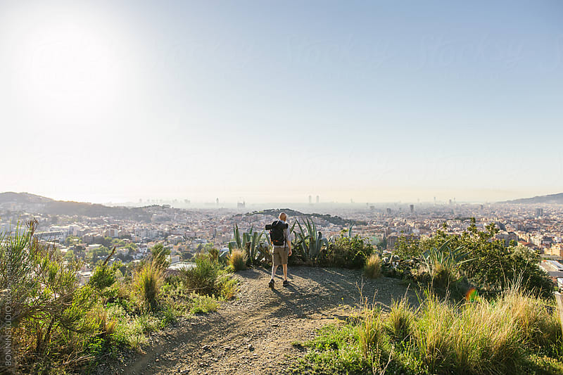 Senior man hiking in a mountain trail over the city. by BONNINSTUDIO for Stocksy United