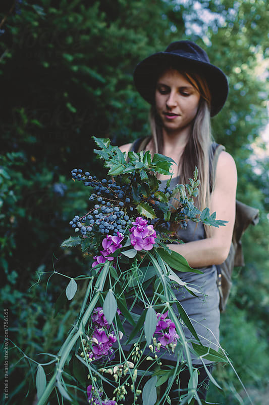 Woman collecting plants and flowers in the woods by michela ravasio for Stocksy United