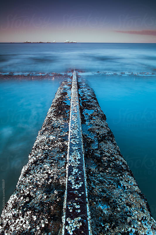 Long exposure old rail track receding into the sea by Micky Wiswedel for Stocksy United