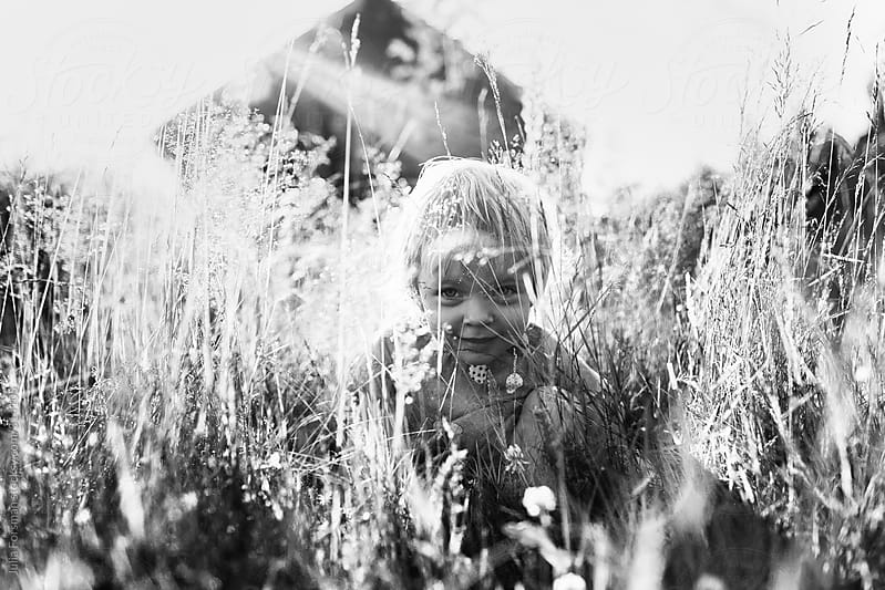 Girl toddler in grass, rural Finland by Julia Forsman for Stocksy United