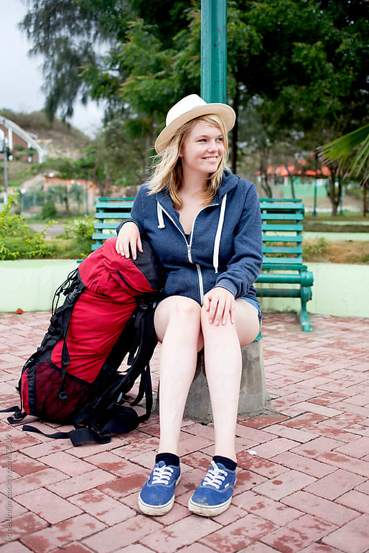 A happy young woman smiling while waiting during a backpack holiday by Ivo de Bruijn for Stocksy United