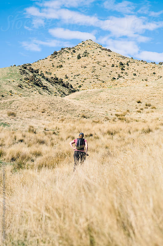 Woman walking up a grass covered hill, New Zealand. by Thomas Pickard for Stocksy United