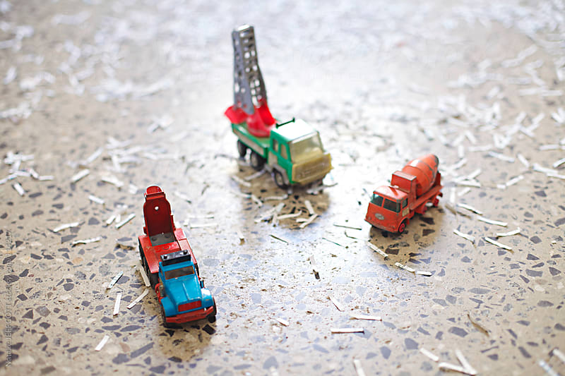 close up of toy trucks surrounded by fake snow / shredded paper by Natalie JEFFCOTT for Stocksy United