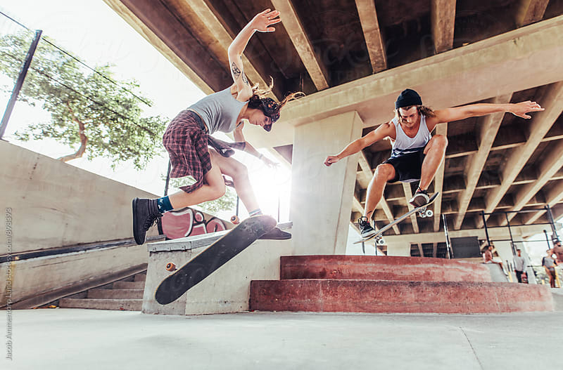 Skateboarders doing big ollie by Jacob Lund for Stocksy United