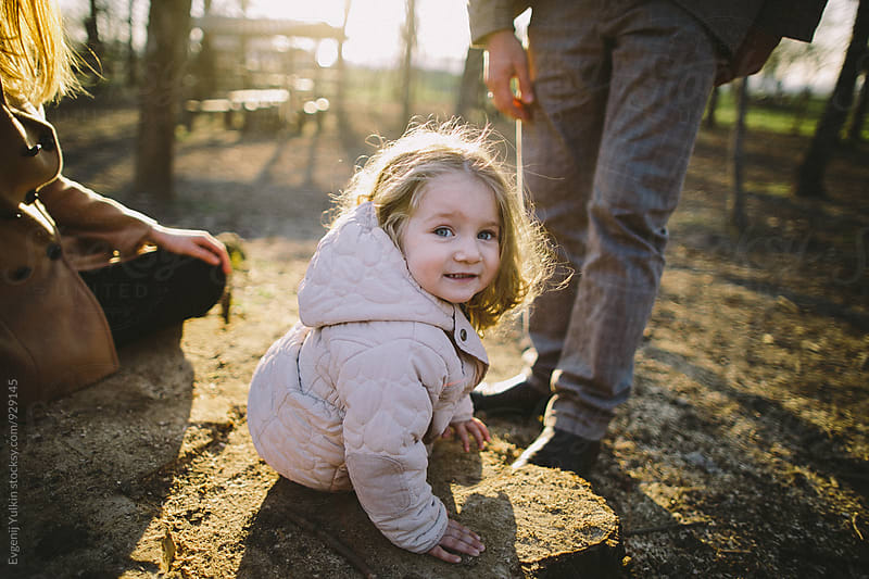 Little girl sitting on the stump looking into the camera by Evgenij Yulkin for Stocksy United