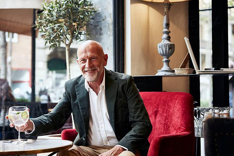 Smiling Senior Man Having Drink In Restaurant by ALTO IMAGES for Stocksy United