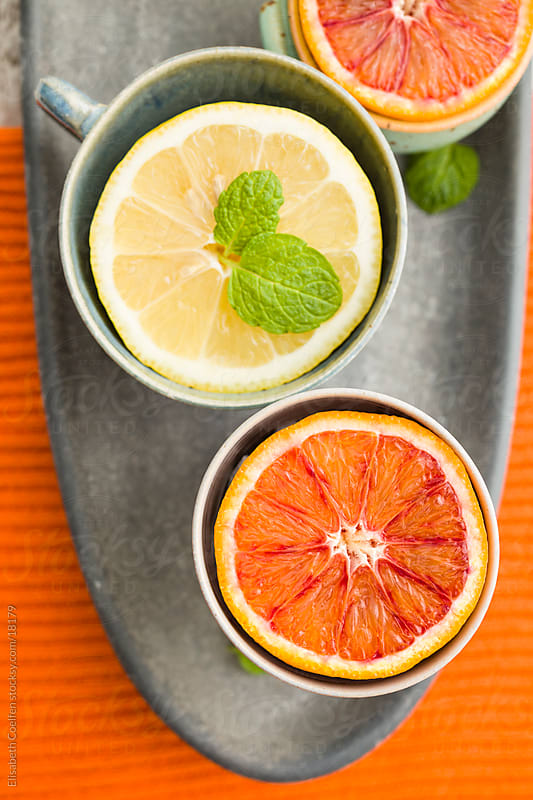Blood orange and lemon halves in cups garnished with mint leaves on oval grey platter by Elisabeth Coelfen for Stocksy United