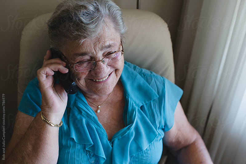 Happy older woman talking on landline phone at home by Rob and Julia Campbell for Stocksy United