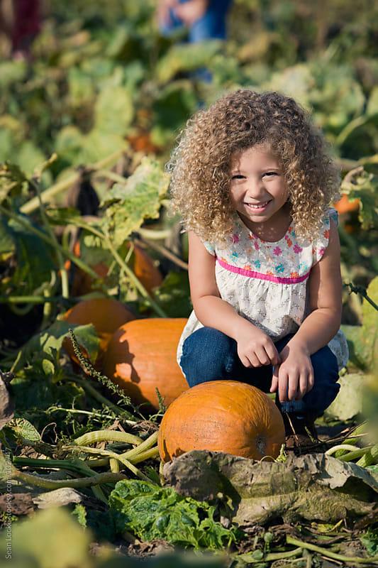 Pumpkins: Cheerful Girl Crouching In Pumpkin Patch by Sean Locke for Stocksy United