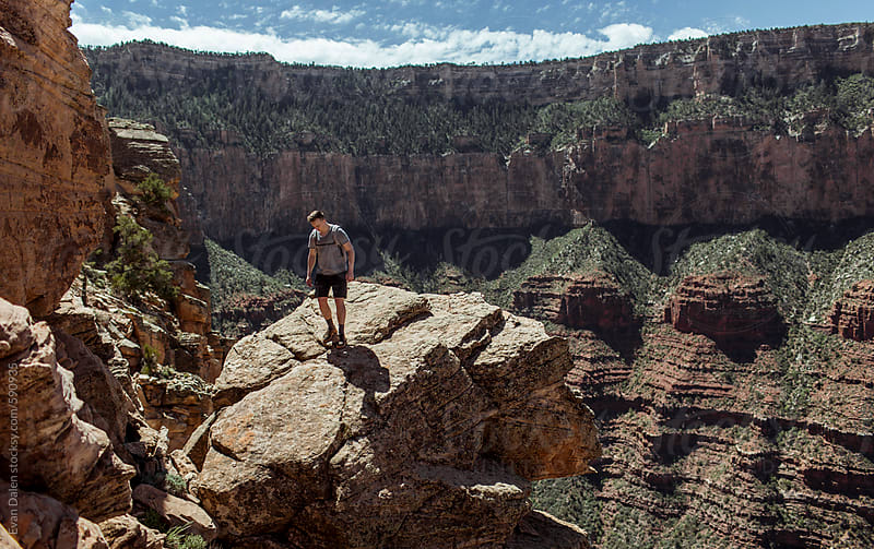 Man Walking On Cliff In Grand Canyon by Evan Dalen for Stocksy United