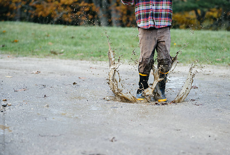 Child wearing rubber boots splashes in a mud puddle by Cara Dolan for Stocksy United