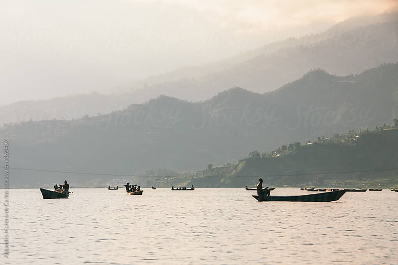 Boats on a lake at sunset. Travel in Pokhara, Nepal by Alejandro Moreno de Carlos for Stocksy United