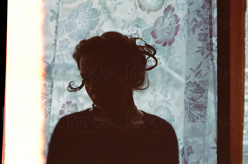 A film portrait of a young beautiful woman in front of the window by Anna Malgina for Stocksy United