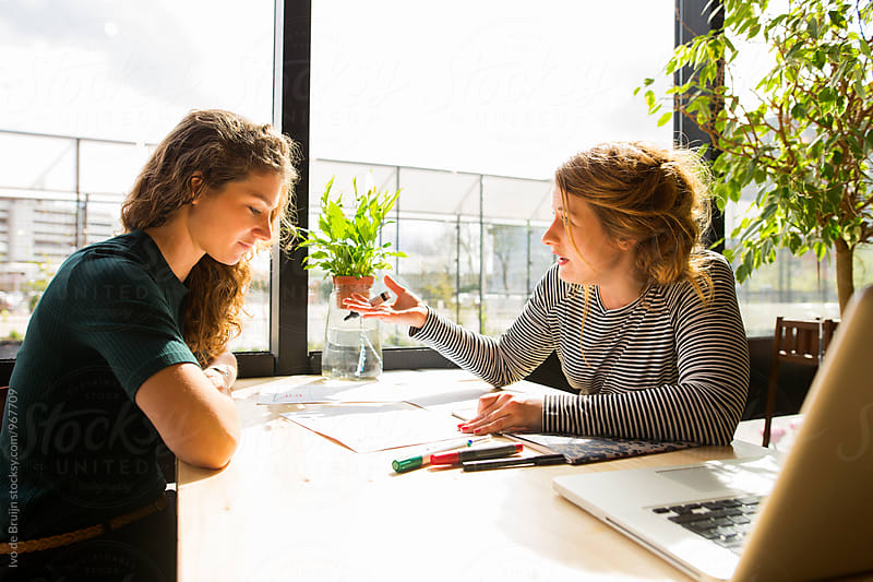 Two young women working, sketching and designing. Using a laptop, sitting at their desk. by Ivo de Bruijn for Stocksy United