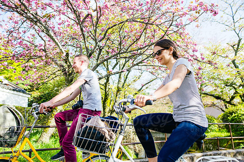 Side view of tourist friends riding their bicycle in spring. by BONNINSTUDIO for Stocksy United