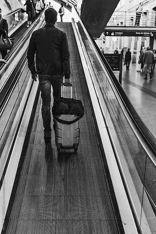Young Businessman Walking Through the Airport Escalators with Luggage by Victor Torres for Stocksy United