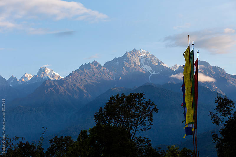 Mountain peaks and buddhist prayer flags in the morning light by Saptak Ganguly for Stocksy United