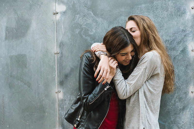 Best girl friends kissing and hugging each other by Simone Becchetti for Stocksy United