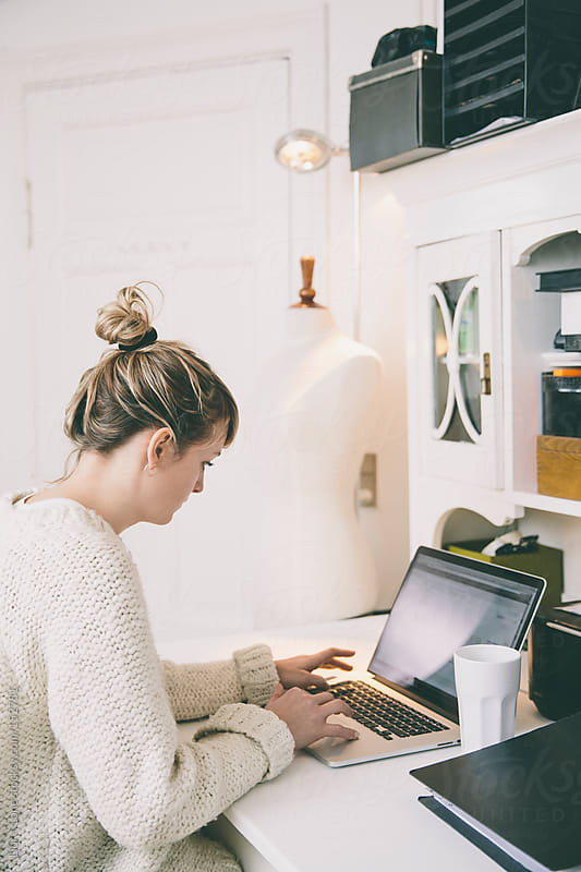 Young woman working on a laptop in home studio by Lior + Lone for Stocksy United