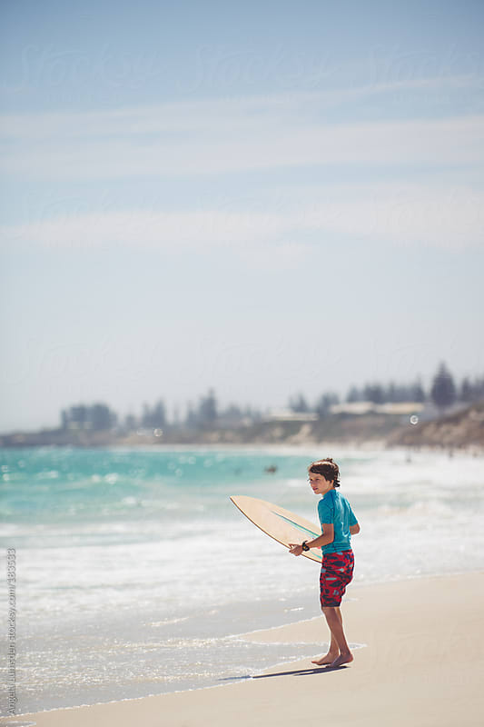 Boy waiting for the right wave for skim boarding by Angela Lumsden for Stocksy United
