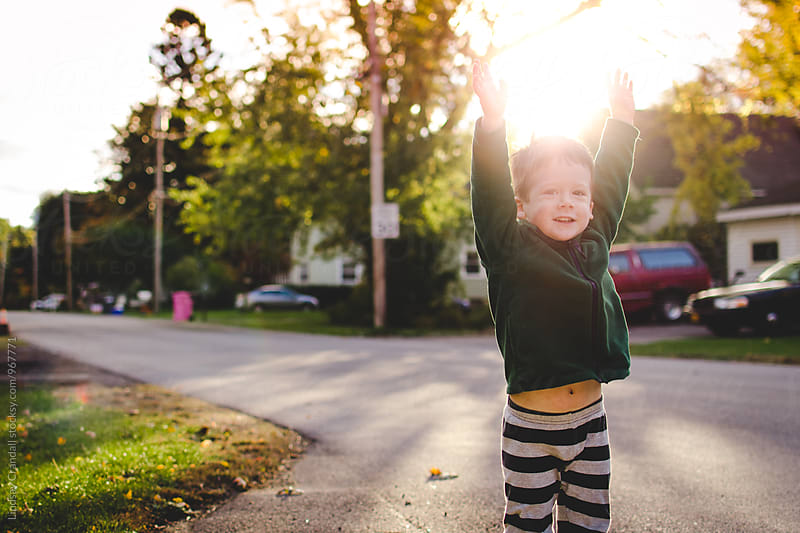 Young child jumping in the sunshine by Lindsay Crandall for Stocksy United