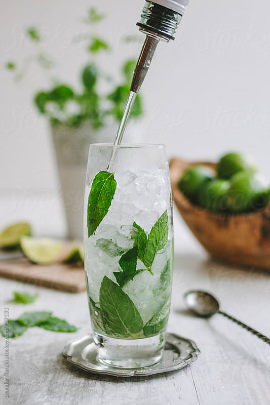 rum pouring into a glass of a mojito cocktail by Leander Nardin for Stocksy United