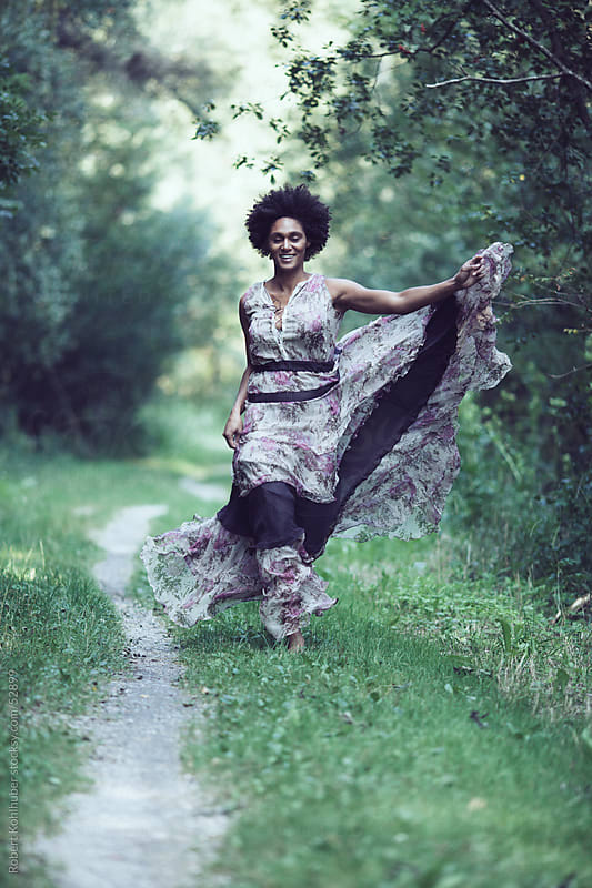 Black woman with dress running in forest by Robert Kohlhuber for Stocksy United